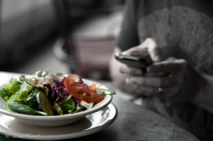 The salad waits while the man tweets.