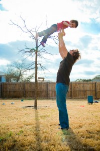 Father throws son in the air.