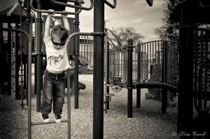 Hanging from the monkey bars.